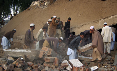 Men help clear the rubble from the site of a suicide bombing in Pakistan's northwest Mohmand region