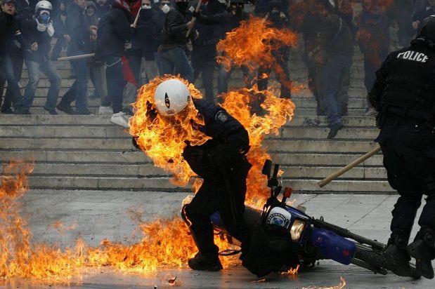 Un policía intenta escapar de las llamas de una bomba que le arrojaron durante los disturbios en Grecia contra las medidas económicas