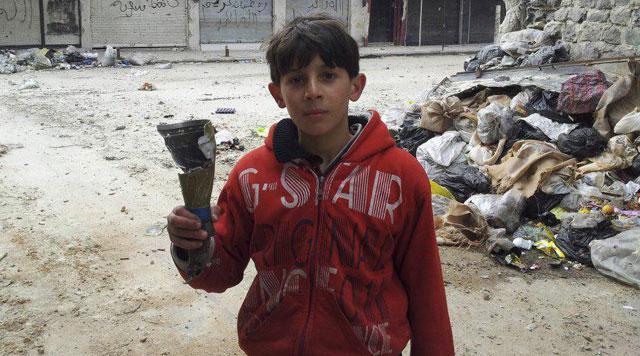 Niño en el barrio de Homs sostiene restos de proyectil |  Reuters