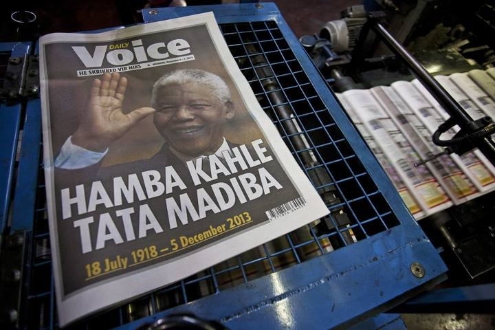 A copy of a newspaper paying tribute to South African President Mandela lies on a printing press as other copies stream through the press in the early hours of the morning in Cape Town