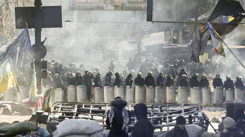 Varios manifestantes permanecen tras una barricada ante un cordón policial en Kiev (Ucrania)    (Foto: EFE)