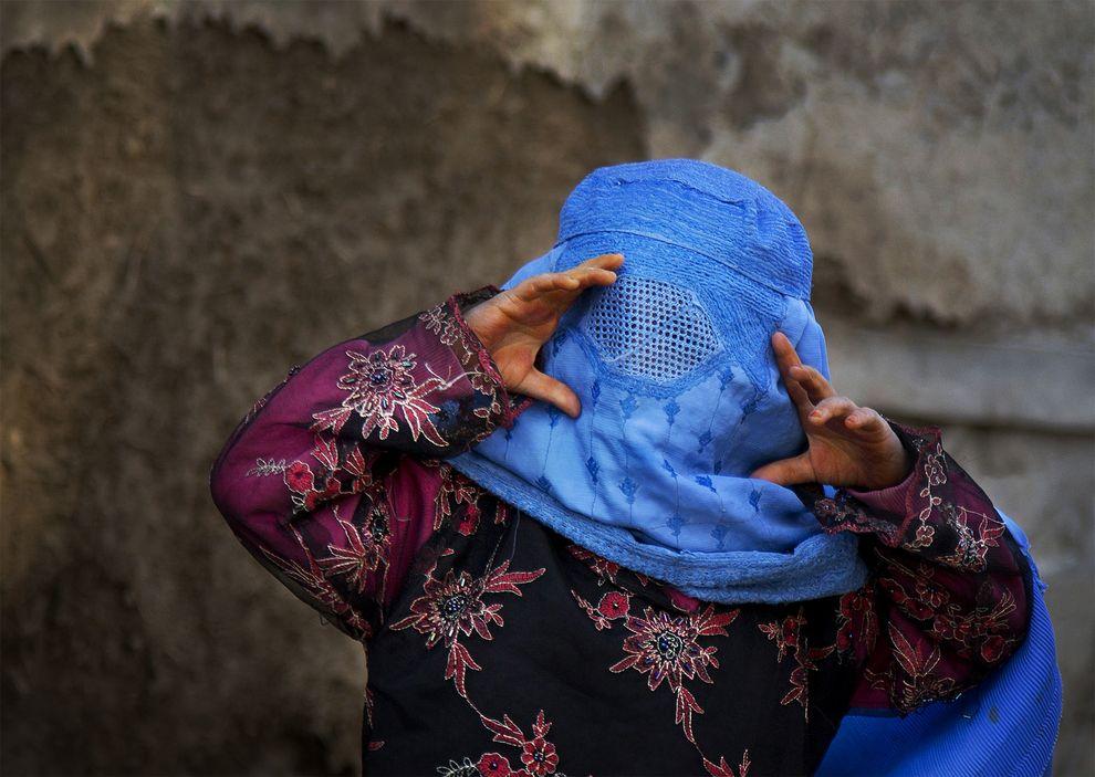 Una niña afgana trata de ver  través de los huecos de su burka mientras juega con otros niños en el pueblo de Kabul.  Foto: Anja Niedringhaus/Abril 2013