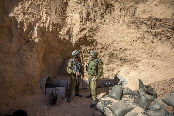 Israeli army officers talk at the entrance of a tunnel said to be used by Palestinian militants for cross-border attacks