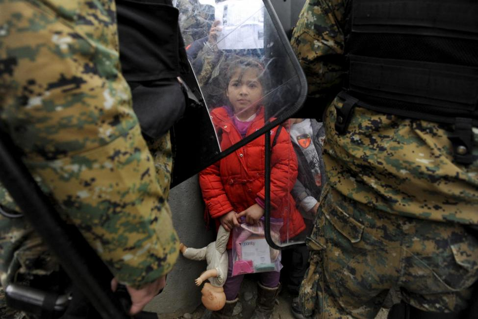 A migrant girl holds her toys as Macedonian policemen block migrants at the Greek-Macedonian borders, near the village of Idomeni, Greece November 20, 2015. REUTERS/Alexandros Avramidis