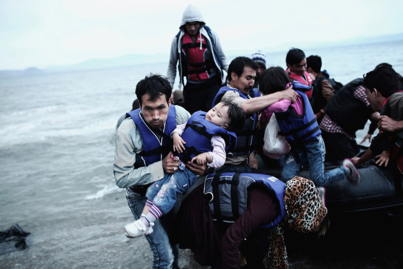 An Afghan refugee carries his child as he arrived on a beach on the Greek island of Kos, after crossing a part of the Aegean Sea between Turkey and Greece, on May 27, 2015.