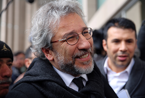 Can Dundar, the editor-in-chief of opposition newspaper Cumhuriyet, speaks to the media before the start of his trial in Istanbul, Friday, March 25, 2016. A group of writers, including Nobel laureates, are calling on Turkey to drop charges against two prominent journalists who face life imprisonment for their reports, and to end its crackdown on free expression. Dundar and Erdem Gul, paper's Ankara representative, go on trial on Friday accused of espionage and other charges for their reports on alleged government arms smuggling to Syrian rebels. (AP Photo/Dominique Soguel)