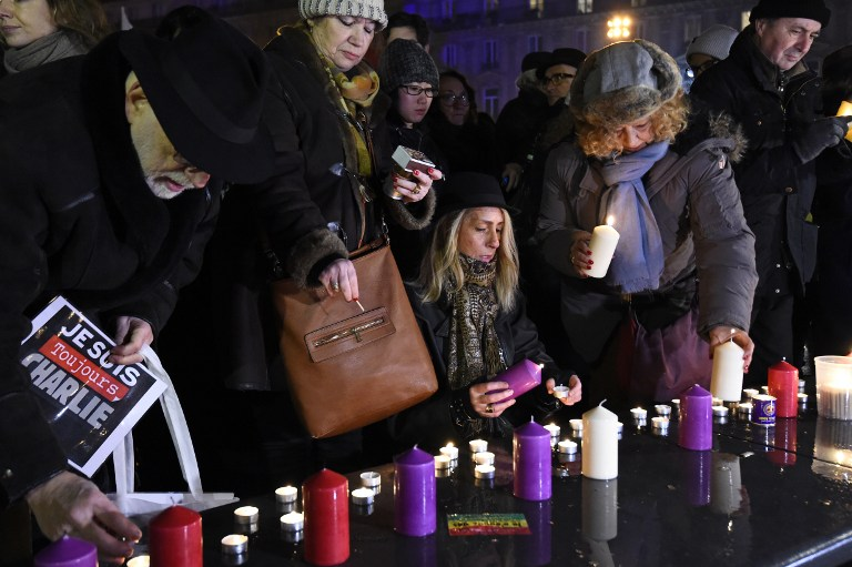 Members of the public light candles during a rally commemorating the second anniversary of the deadly attack against the satirical weekly Charlie Hebdo on January 7, 2017 at the Place de la Republique in Paris. Almost two years after the attacks of January 2015 on French satirical magazine Charlie Hebdo and the Hyper Cacher market, which left 17 people dead and were the first in a series of jihadist attacks in France, investigators are still working to shed light on certain aspects of the events, including the complicity of the killers. / AFP PHOTO / BERTRAND GUAY