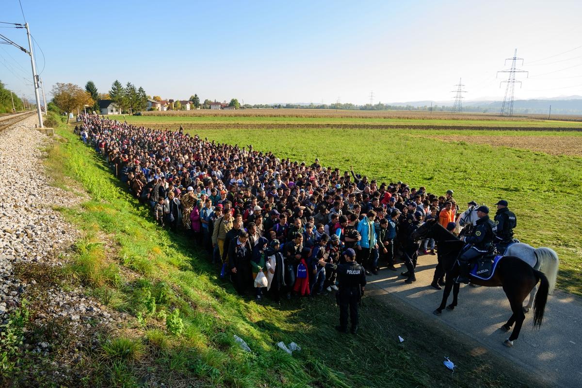 La policía escolta a miles de migrantes y solicitantes de asilo mientras se dirigen a un campo de refugiados tras cruzar la frontera entre Croacia y Eslovenia, cerca de Rigonce, el 24 de octubre de 2015. (AFP / Jure Makovec)
