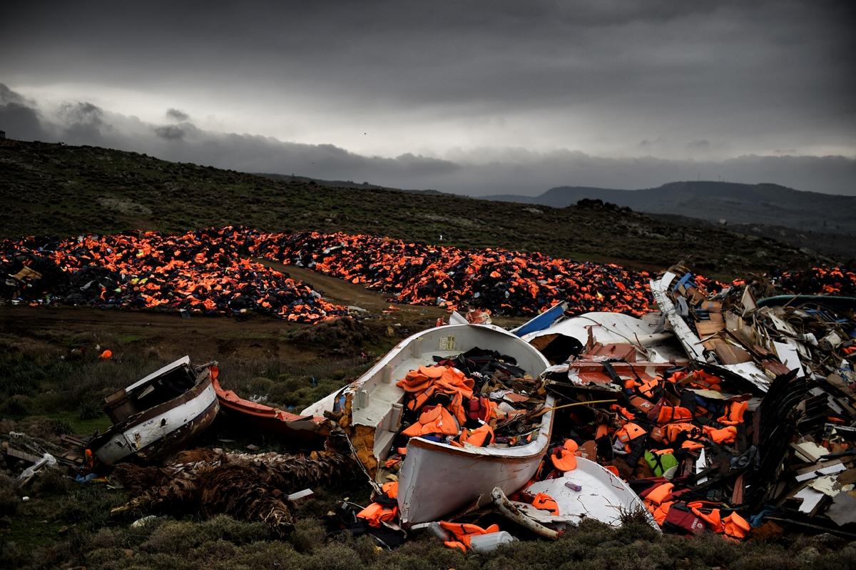 Botes destruidos y miles de chalecos salvavidas, usados por migrantes para cruzar el mar Egeo, quedan tirados en Mithimna, el 19 de febrero de 2016. (AFP / Aris Messinis)